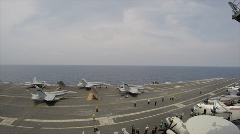 A cluster of fighter jets waiting to take-off on the USS Carl Vinson.