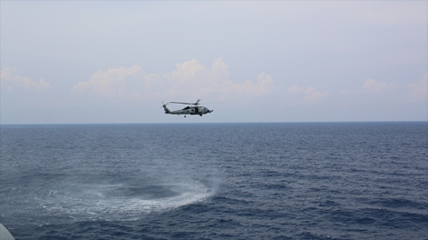 A Sea Hawk helicopter hovering over the South China Sea.