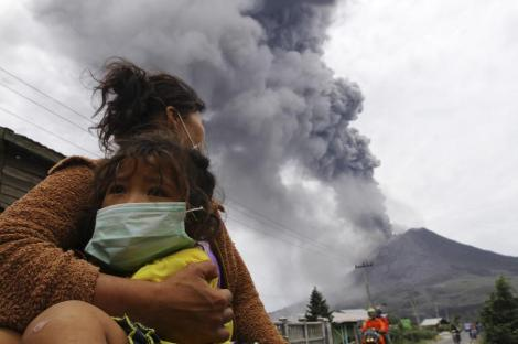 A mother holds her child as Mount Sinabung spews ash and hot lava during an eruption in Perteguhan village in Karo district, September 17, 2013.  REUTERS/Roni Bintang