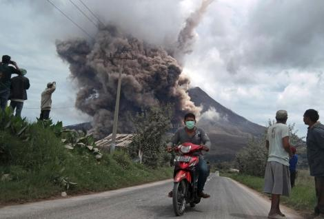 A resident rides his motorcycle as Mount Sinabung spews ash at Namanteran village in Karo Regency, Indonesia's North Sumatra province, June 16, 2015.  REUTERS/Antara Foto/Irsan Mulyadi